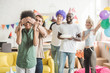 Young men and women covering eyes of young female friend and greeting her with birthday cake on surprise party