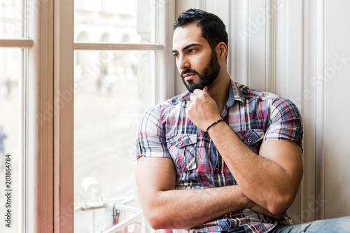 Foto Murales Portrait of handsome bearded man sitting on wide white windowsill