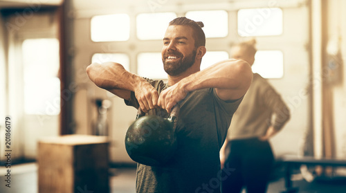 Fototapeta Fit young man smiling while lifting dumbbells in a gym