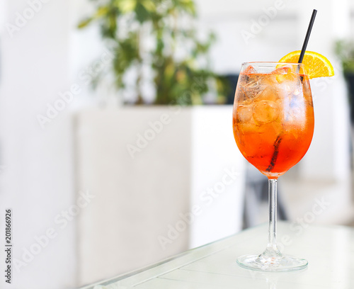 Orange cocktail with straw on white table