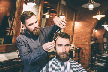A picture of two bearded guys are in a barbershop. The hairdresser is cutting the hair of his customer using scissors and small hair brush.