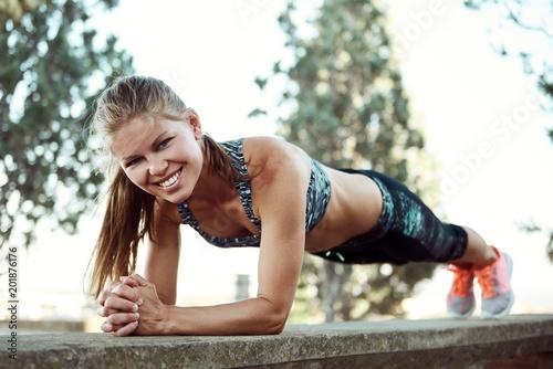 Dosyć uśmiechający się żeńskiej atlety pozycję w deski pozyci plenerowej. Sport, fitness i styl życia.