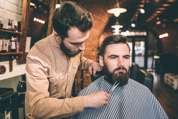 Customer is sitting in chair and looking straight forward with a serious sight. His airstylist is cutting his beard with scissors.