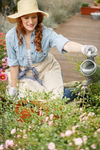 Foto Murales Smiling gardener woman watering flowers