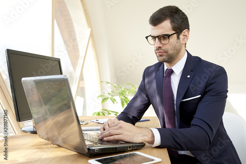 Foto Murales Young businessman typing on notebook