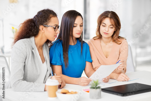 Fridge magnet business, teamwork and people concept - female team or businesswomen discussing papers at office