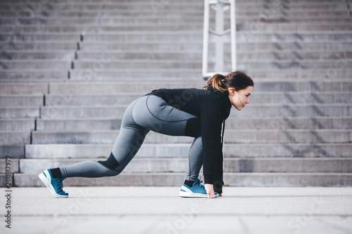 Foto Murales Sportswoman in a starting position, ready to run