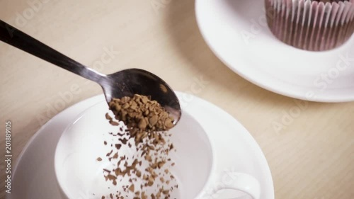 Wall mural Slow motion soluble coffee with a spoon to pour into the cup and move the camera to the muffin
