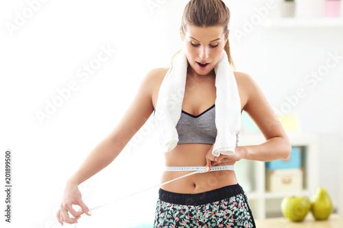 Foto Murales Woman measuring waist after workout