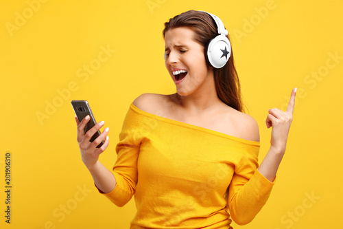 Foto Murales Beautiful woman listening to music on smartphone over yellow background