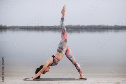 Morning yoga and pilates .Young healthy woman practicing yoga on the beach at sunrise.