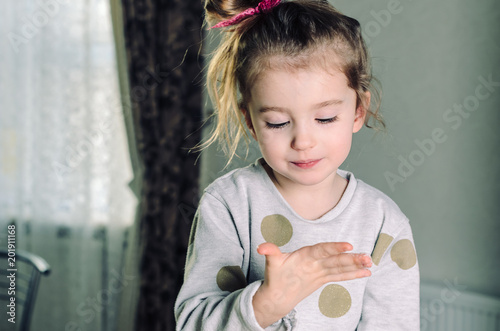 A small beautiful and contented girl with long eyelashes looks at her palm, fingers stained with sugar.