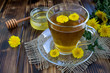 Tea with  dandelions in the glass cup on the rustic wooden background