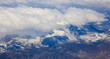 Snowy mountains background and white clouds above them. Aerial photo from plane's window. - 201921555