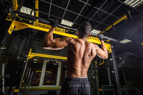 lekkoatletycznego african american człowiek robi pull-up w siłowni na belce. power pull Up trening. jak wygląda mięśnie podczas ciągnięcia
