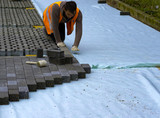 Construction worker laying interlocking paving concrete onto sheet nonwoven bedding sand and fitting them into place. - 201975529