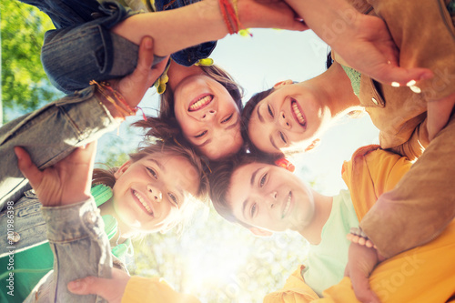 Leinwandbild Motiv friendship and people concept - group of happy teenage friends holding hands outdoors