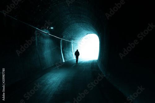 Mężczyzna idzie sam w ciemnym tunelu ze światłem na końcu.