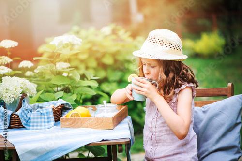 Fridge magnet happy child girl drinking tea with lemons in summer garden in the morning.