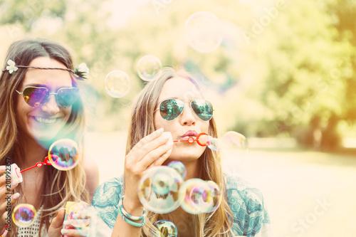 canvas print picture freundinnen machen seifenblasen in einem park. zwillinge