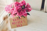 happy mother's day text on craft card and pink peonies bouquet on rustic white wooden window in light. floral greeting card concept. mothers day. soft tender spring image - 202008146