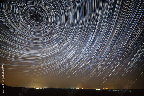 Star trails in the night sky. A view of the starry space and the light above the skyline.