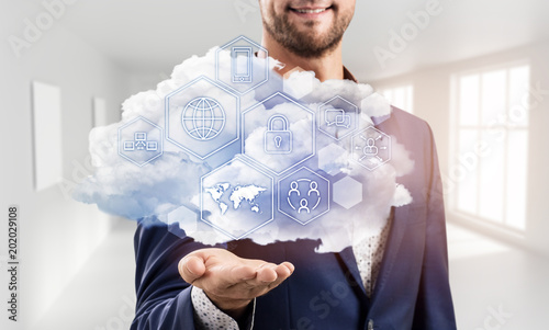 Foto Murales Businessman holding cloud with different digital icons.