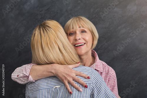Szczęśliwy dorosły matki i córki obejmowanie na szarym tle