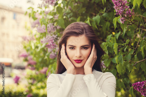 Foto Murales Perfect young woman with makeup on floral background outdoors