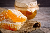 Honey background. Sweet honey in the comb, glass jar. On wooden background.