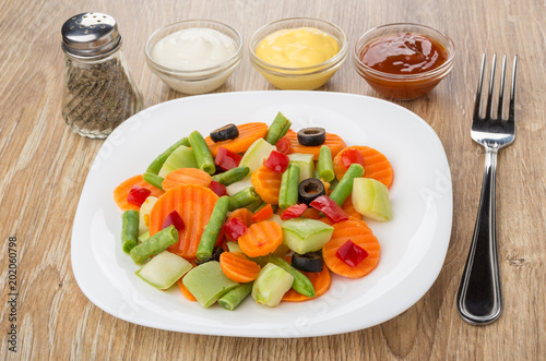 White plate with vegetable mix, bowls with sauce, pepper - 202060798
