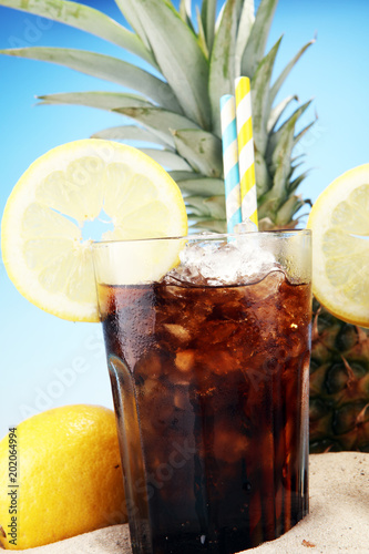 Foto Murales Softdrink with ice cubes, lemon and straw in glass.