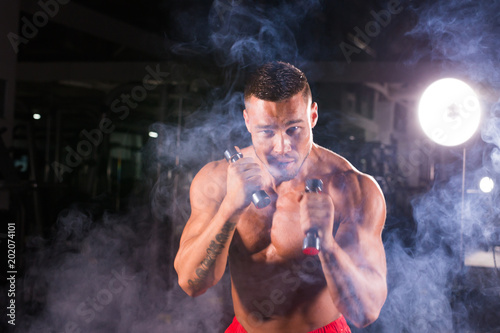 Poster Powerful man doing boxing exercises, making direct hit with dumbbells. Photo of sporty muscular male. Strength and motivation