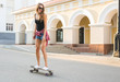 Beautiful young hipster woman with skateboard outdoors