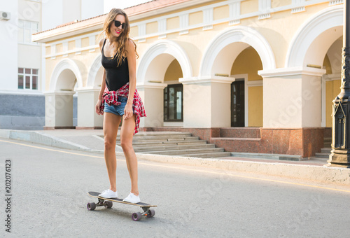 Plexiglas Skateboard Beautiful young hipster woman with skateboard outdoors