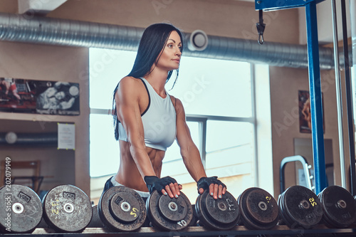 Foto Murales Beautiful sexy athletic brunette female in a sportswear standing near the counter with dumbbells in the gym.