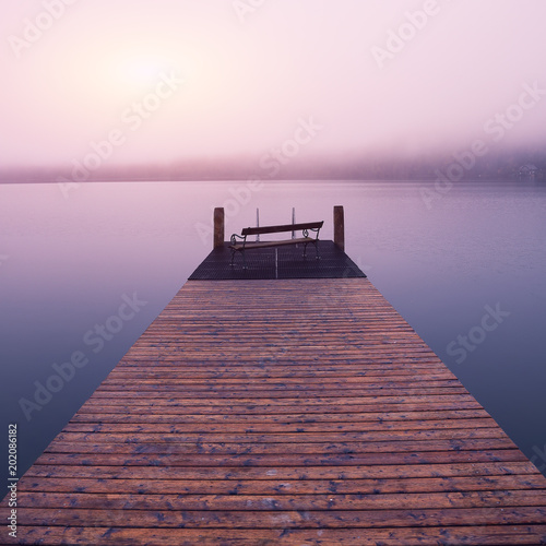 Acrylglas Pier Empty footbridge with a bench on a lake Altausseer at sunrise