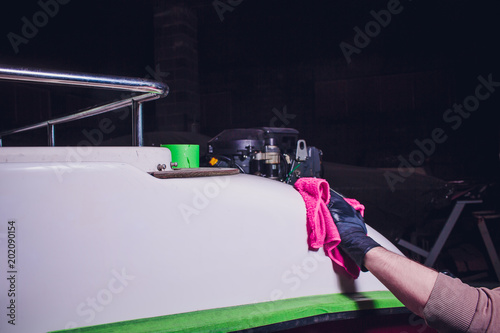 Foto Murales Man washes deck yacht with pink rag. preparation in polishing, repair yacht, boat