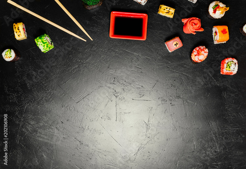 Top view of Japanese Sushi and chopsticks on black background. Sushi rolls, nigiri, maki, pickled ginger, wasabi, soy sauce. Space for text. Top view. Sushi background. food frame