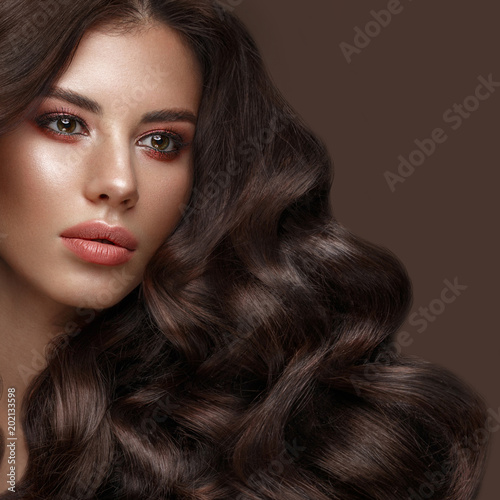 Beautiful brunette model with curls, classic makeup and full lips. The beauty of the face. Portrait shot in the studio.