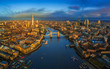 London, England - Panoramic aerial skyline view of London including iconic Tower Bridge with red double-decker bus, Tower of London, skyscrapers of Bank District at golden hour early in the morning