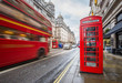 London, England - Iconic blurred vintage red double-decker bus on the move with traditional red telephone box in the center of London at daytime