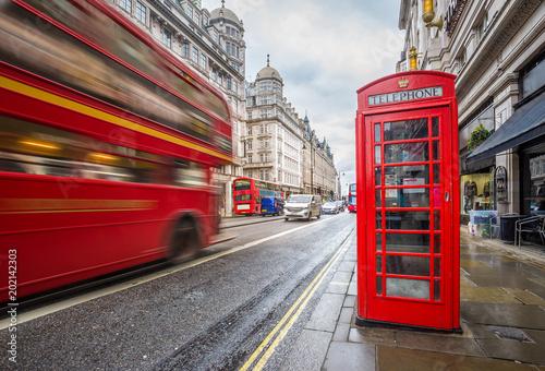 Londyn, Anglia - Iconic niewyraźne vintage czerwony piętrowy autobus w drodze z tradycyjnych czerwonych budki telefonicznej w centrum Londynu w ciągu dnia