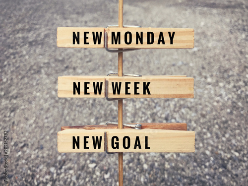 Motivational and inspirational quote. Words 'New Monday, new week, new goal' on wooden cloth clips.