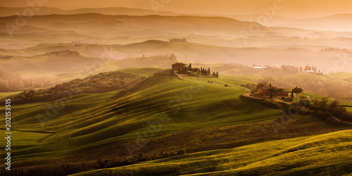 Fotobehang Toscane Beautiful landscape in Tuscany in Italy with fog during sunrise and hills in the background and green fields