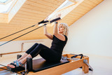 Pilates reformer eldery blond curly woman gym fitness teacher workout back and hands exercise on pilates reformer device - pilates, fitness, sport, training and people concept.