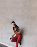 Woman in sportswear standing by a wall
