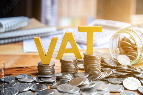 Vat Concept.Word vat with stacked coins there is a notebook calculator on the desk.VAT