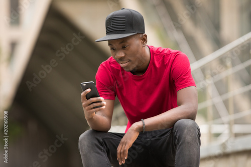 Young man in pink t-shirt use smart phone app in city street