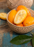 Delicious small citrus fruits kumquats close up on wooden table - 202181793